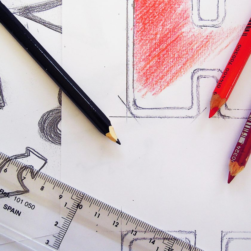 Färgpennor och linjal liggande på ett papper med skisser för logotyper.