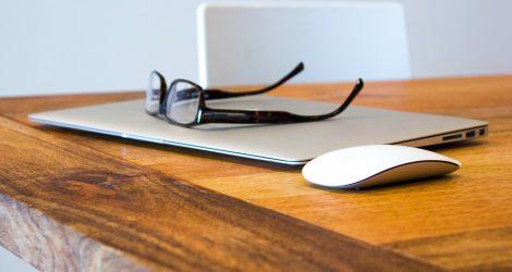 Ett par glasögon liggande på en laptop-dator.