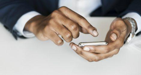 En mobiltelefon hålls i en hand, medan de andra handen pekar på den.