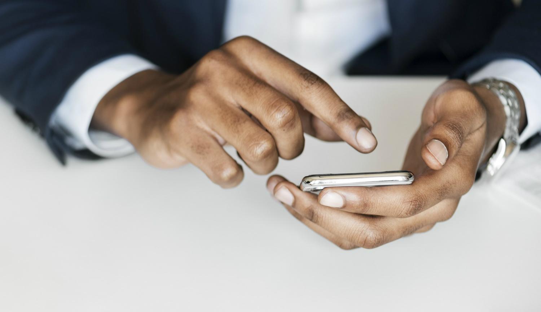 En mobiltelefon hålls i en hand, medan den andra handen pekar på den.