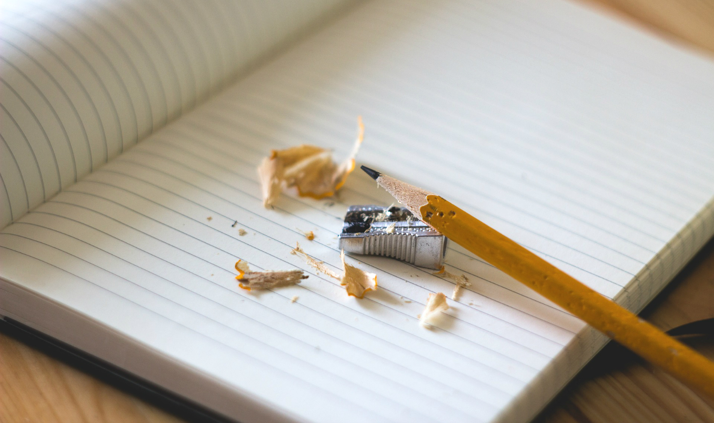 Penna och pennvässare ligger på en skrivbok