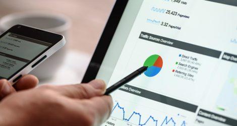 En hand pekar på en datorskärm med statistik över datatrafik och besökare