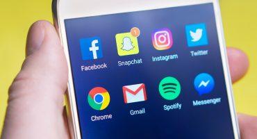 En hand håller i en mobiltelefon där skärmen visar olika sociala medier-applikationer