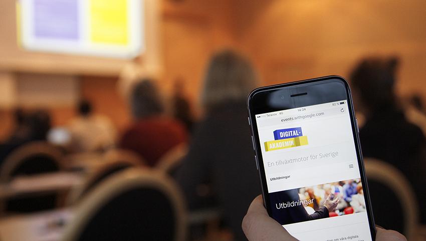 Mobiltelefon med Digitalakademins webbplats, i bakgrunden en föreläsning med Digitalakademin