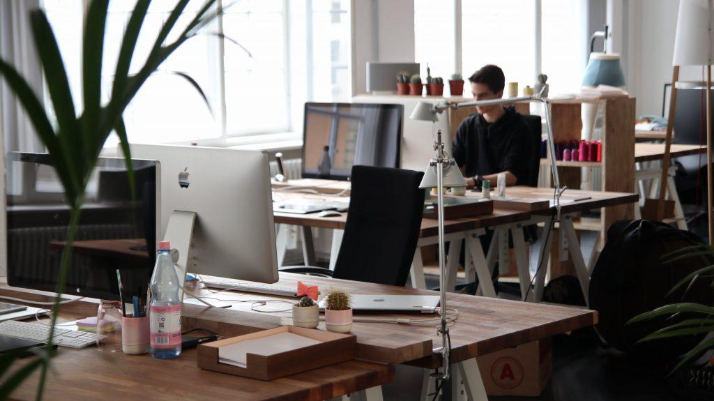 Vy över kontorslandskap, man ser en kille som sitter i bakgrunden och jobbar